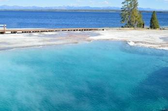 A clear, blue, steamy hot spring next to Yellowstone Lake at the West Thumb Geyser Basin.